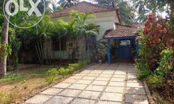 A resale 2 BHK Portuguese house for sale in a gated compound, located in a prime location in Calangute, North Goa. It has an independent open car park space within the compound. There are coconut plantations and floral plants in the plot. It is in close