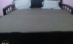 Black Wooden Bed Frame With Grey And White Bed Sheet