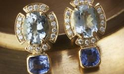 Classic pair of diamond earrings featuring blue