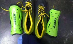 Pair Of Black And Yellow Cleats And Pair Of Shin Guard